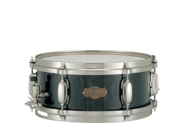 """Simon's main snare drum, """"The Monarch"""", produces never-heard-before tones thanks to its 8ply maple/bubinga/maple hybrid shell and customized triple flanged hoops. This combination provides a warm controlled sound with sharp, bright cut. His second main snare drum, the Gladiator, features black nickel-plated bronze shell. His Pageant maple drum completes Simon's snare drum arsenal."""